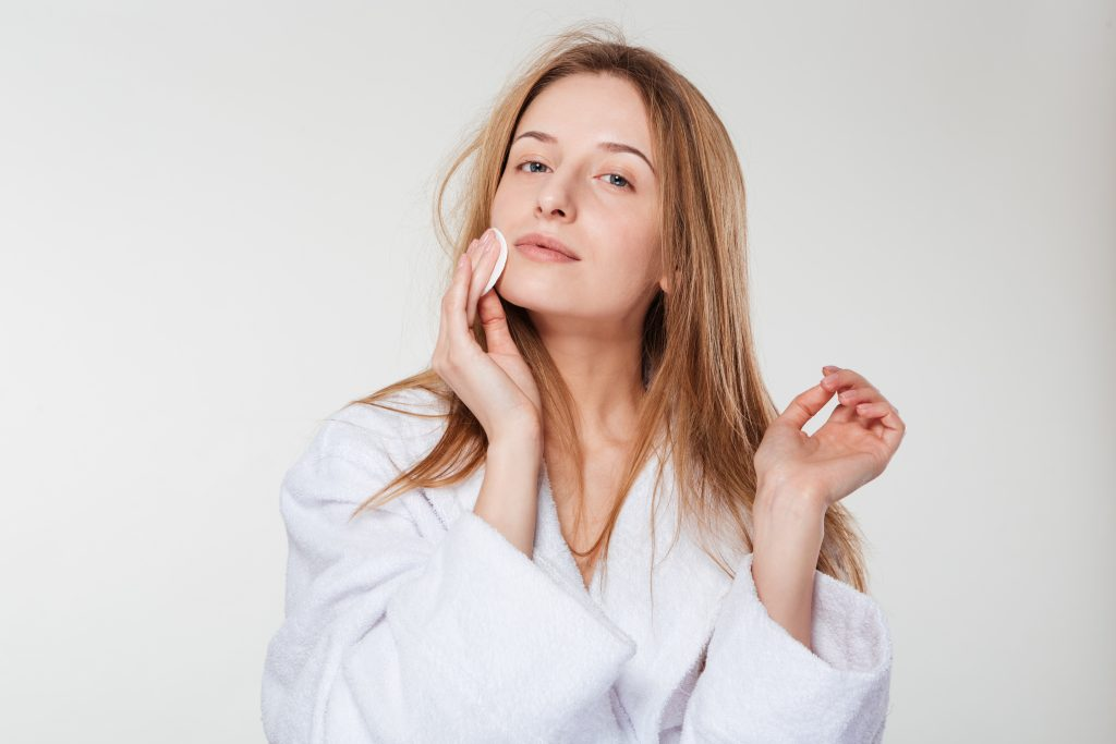 Beautiful woman cleaning face with cotton pad isolated on a white background
