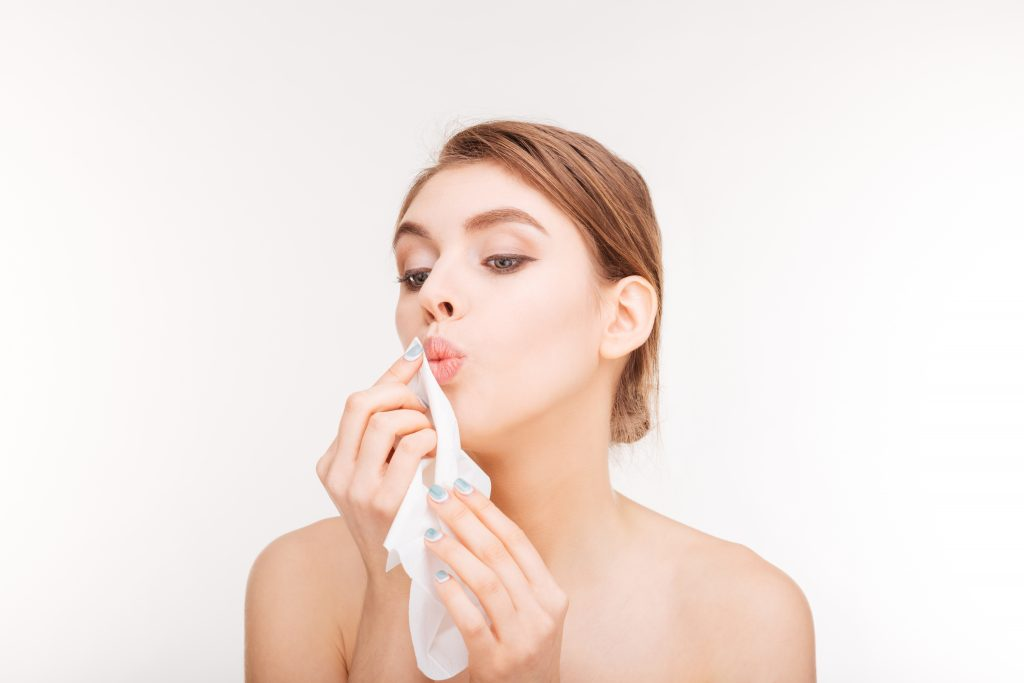 Beauty portrait of cute lovely young woman applying paper napkin to her lips over white background
