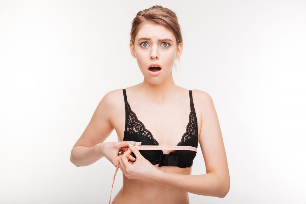 Amazed stunned young woman in black bra measuring her chest over white background